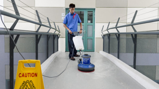 Cleaning personnel clean the floor with a device