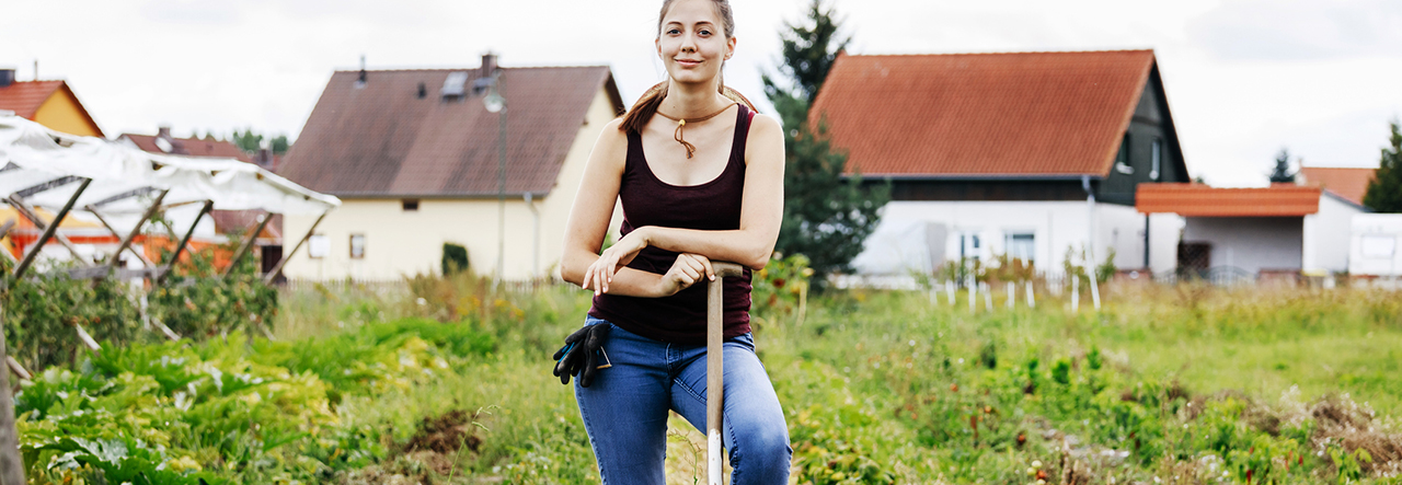 Woman standing in the field with pitchfork