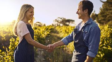 A man and a woman wear aprons over their clothes and shake their hands.