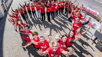 Group of people wearing stop-hunger T-shirts that stand and wave in the shape of a heart.