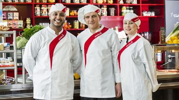 Three Sodexo chefs stand in front of a bar.